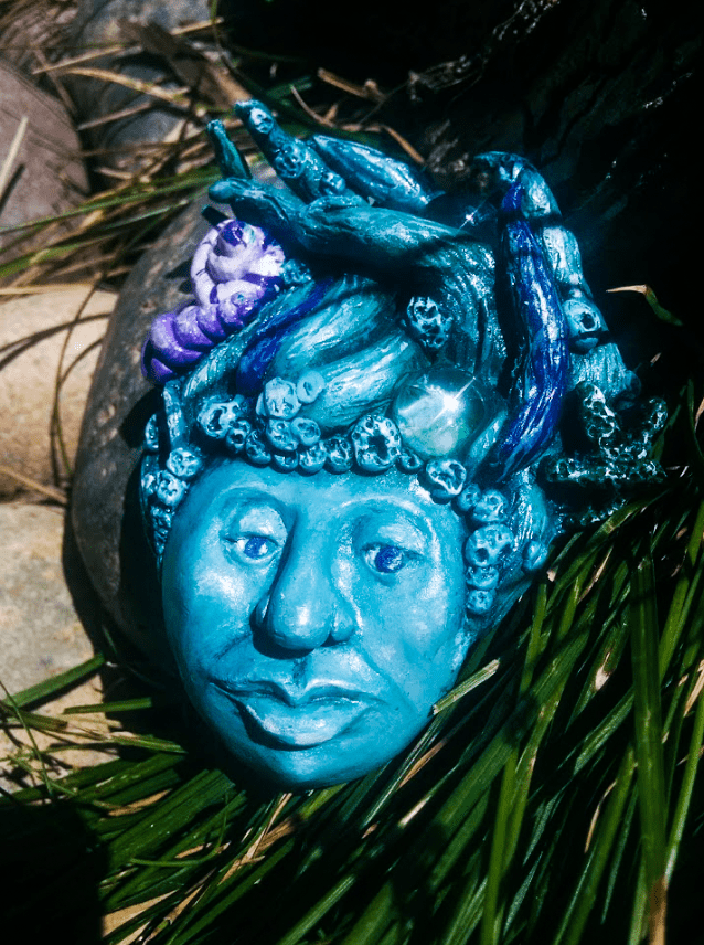 A peaceful, shimmering blue dryad rests in the shade; her water gems winking in the sun