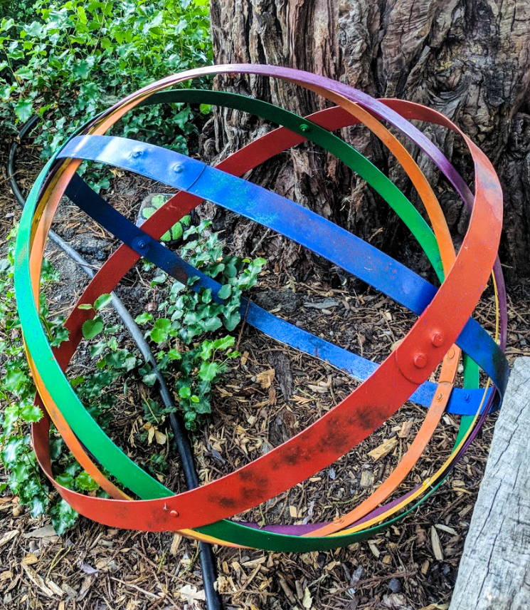 A colorful orb made of upcycled wine barrel rings, painted and nested like a ball of string.