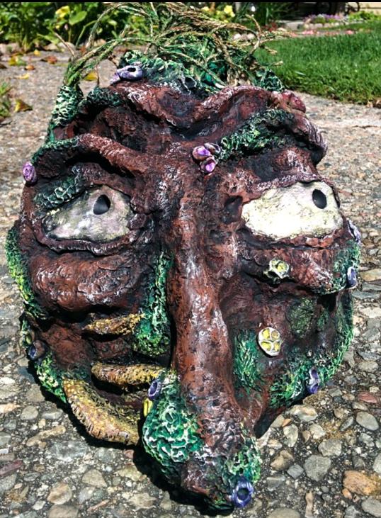 A lumpy mud troll looks up from the sidewalk.